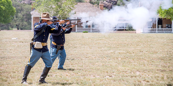 Cavalrymen fire rifles at the Fort Davis National Historic Site.